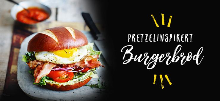 Pretzelinspirert burgerbrød oppsmurt med egg, salat og tomater